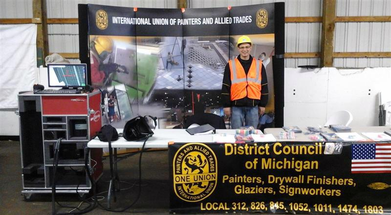 DC 1M U.P. Representative Travis Cary at a job fair in Houghton/Hancock Michigan.  Students use SIM paint sprayer unit with Business Manager Robert Gonzalez.